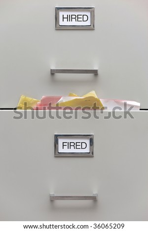 Close up shot of a filing cabinet with labels reading hired and fired.  The 'fired' drawer is very full.  Vertically framed shot. - stock photo