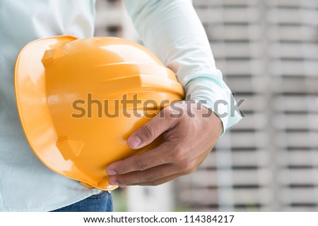 Close-up shot of a foreman holding a hardhat on the construction site - stock photo