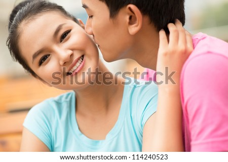 Close-up shot of a guy being about to kiss his girlfriend on the cheek - stock photo