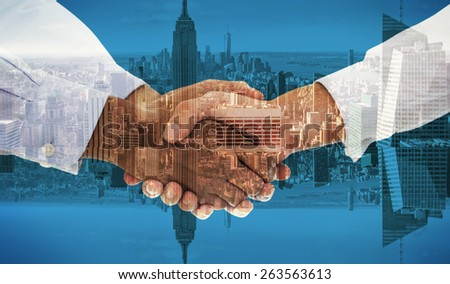 Close-up shot of a handshake against room with large window looking on city - stock photo
