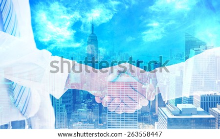 Close-up shot of a handshake in office against city skyline - stock photo