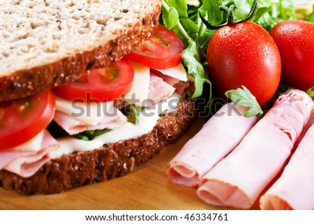 Close-up shot of a healthy ham, cheese, tomato, mayo, and rocket sandwich. - stock photo