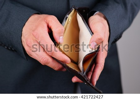 Close up shot of a male businessman showing empty wallet. - stock photo