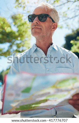 Close up shot of a mature man with a map while standing outdoors in the city on a summer day. Tourist holding a city map and looking away. - stock photo
