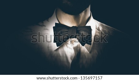 Close-up shot of a model man wearing classy bow tie, getting ready for a party, dinner or wedding - stock photo