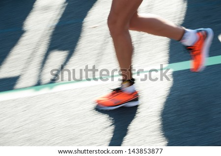 Close-Up shot of a runners feet while running. Longtime Exposure was used to visualize the motion - stock photo