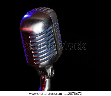 Close up shot of a vintage microphone with reflection of colored lights with a black background - stock photo