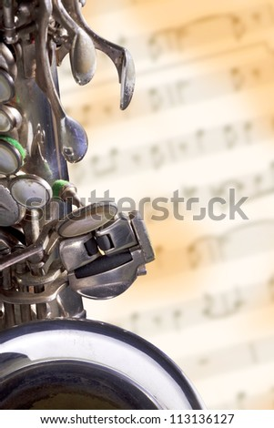 Close up shot of a vintage silver alto saxophone on blur grunge music sheet background - stock photo