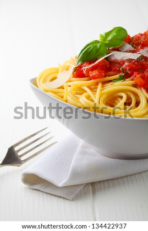Close up shot of a white bowl of pasta with tomato sauce and fresh basil with a white napkin and fork. - stock photo