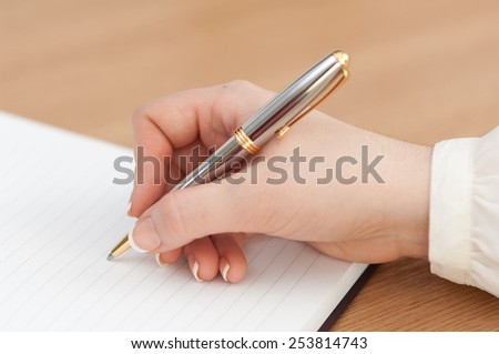 Close-up shot of a woman's hand writing her schedule on the notebook. - stock photo
