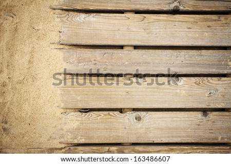 Close up shot of a wooden beach path texture with some sand - stock photo