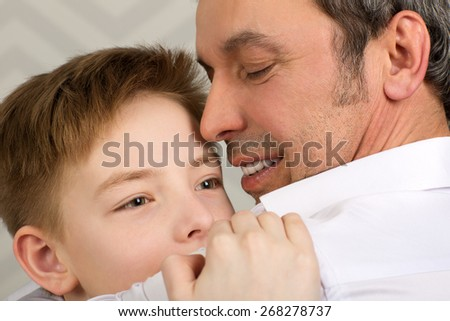 Close-up shot of an emotional embrace of son and father. Happy and close-knit family  - stock photo