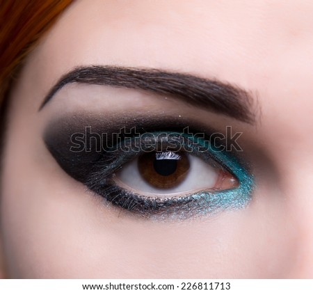 Close-up shot of an eye with artistic blue and black makeup  - stock photo