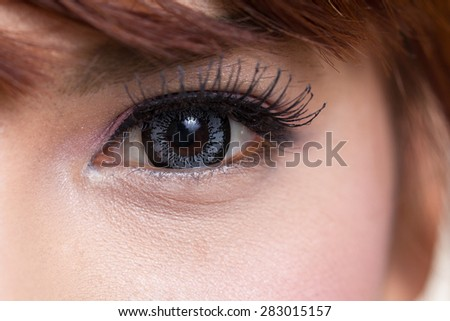 Close-up shot of asian woman eye with contact lens gray colour - stock photo