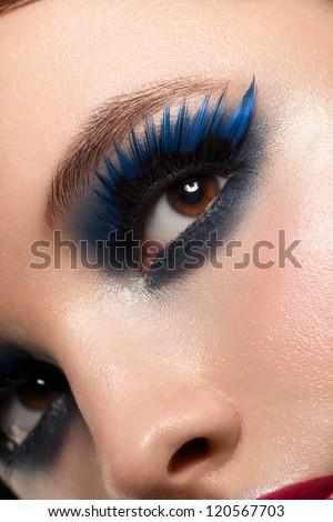 Close-up shot of beautiful female eye with bright fashion makeup. Woman eye with blue false eyelashes - stock photo