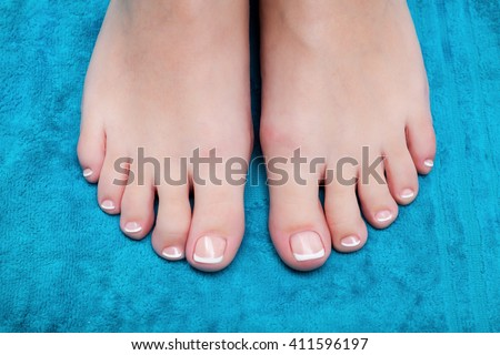 Close-up shot of beautiful woman feet with French pedicure on blue towel - stock photo