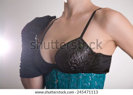 Close-up shot of beautiful young woman in black bra and blue corset in vintage colors  - stock photo