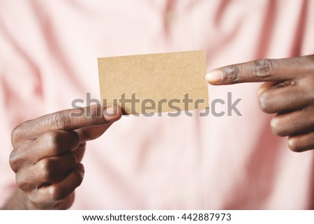 Close up shot of blank modern parchment business card with copy space for your text or promotional content. African entrepreneur in pink shirt holding a visiting card with both index fingers - stock photo