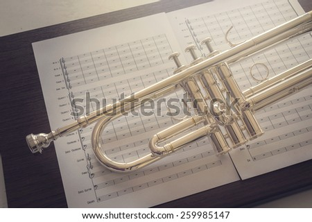 close up shot of body trumpet and blank music note on soft focus and def of field effect  - stock photo