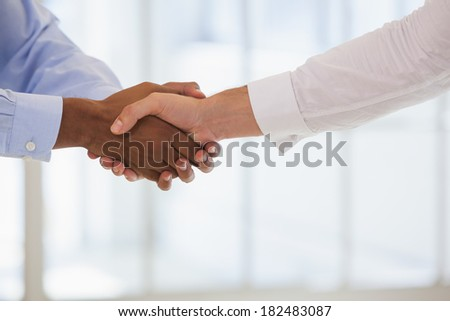 Close-up shot of business people shaking hands in the office - stock photo