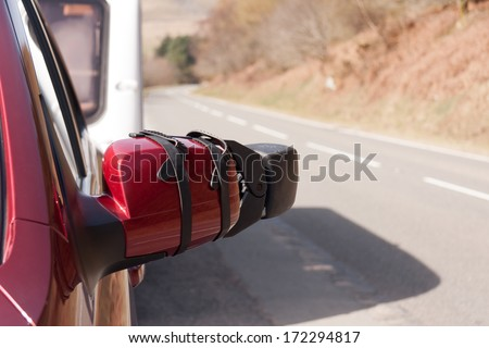 Close up shot of car with caravan mirrors towing caravan parked in lay by looking back down empty road whilst travellng  - stock photo