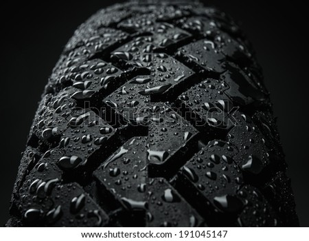 Close-up shot of classical motorcycle tire tread in wet weather condition  - stock photo