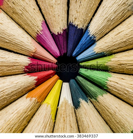 close up shot of colored pencil pointing to the middle  - stock photo