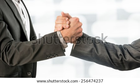 Close up Shot of Conceptual Two Business Partners in Gray Formal Suits Gripping their Hands. - stock photo