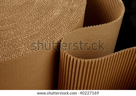 close up shot of corrugated packing material uncurling on black background - stock photo