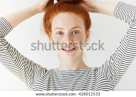 Close up shot of cute redhead freckled student girl relaxing and having fun indoor after classes at university. Young female in trendy sailor shirt, looking at camera with happy and joyful expression - stock photo