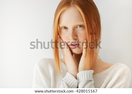 Close up shot of cute redhead teenage girl with perfect freckled skin and blue eyes wearing casual clothes, with hands on her cheeks, looking at the camera with serious expression on her face  - stock photo