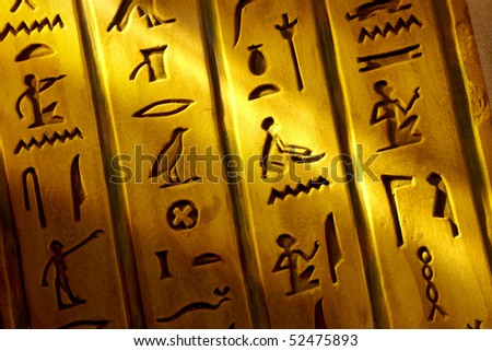 Close up shot of Egyptian hieroglyphics carved into stone with shaft of light - stock photo