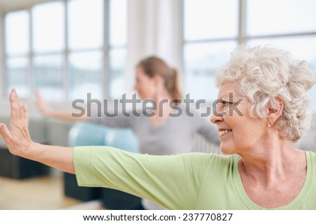 Close-up shot of elderly woman doing stretching workout at yoga class. Women practicing yoga at health club. - stock photo