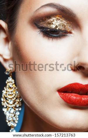 Close-up shot of female face with vogue golden shining eye makeup - stock photo