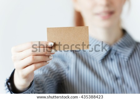 Close up shot of female hands with beautiful manicure, holding a blank business card with copy space for your promotional content. Young redhead businesswoman showing a parchment card at the camera - stock photo
