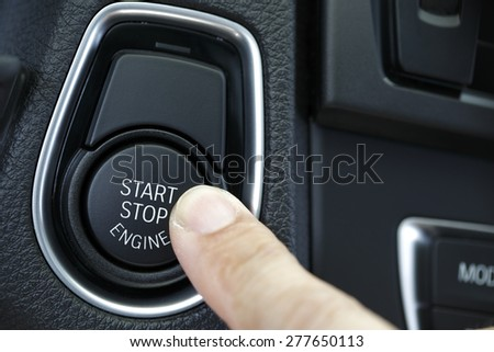Close up shot of finger pressing the start/stop engine button on a car - stock photo