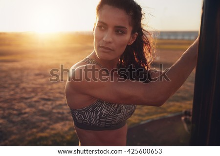 Close up shot of fit young woman in sports bra looking away. Pensive fitness female standing outdoors on a sunny day. - stock photo
