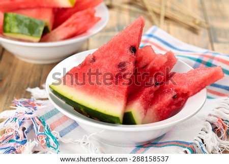 Close-up shot of fresh sliced watermelon in plate. On rustic wooden table. - stock photo