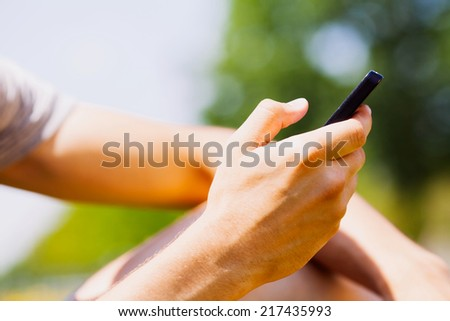 Close-up shot of hand holding mobile phone over blurred nature background - stock photo