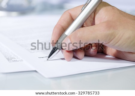 Close-up shot of hand signing a document with a silver pen. Concept of business and agreement - stock photo