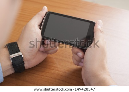Close-up shot of hands of a businessman using a smartphone. - stock photo