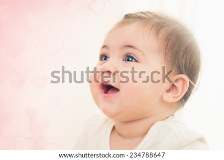 Close up shot of happy smiling baby girl with blue eyes. Soft focus. - stock photo