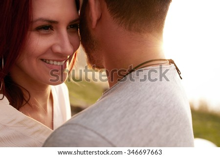 Close up shot of happy young woman embracing her boyfriend and looking away smiling. Loving young couple outdoors. - stock photo