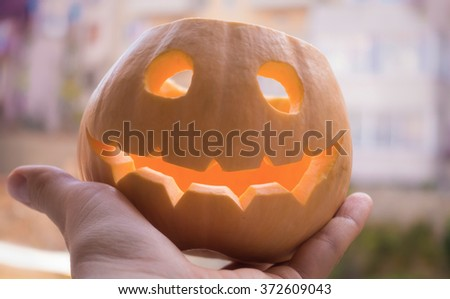 Close up shot of Jack o'Lantern Halloween pumpkin smiling widely in human hand with a blurred autumn street view in the background. - stock photo
