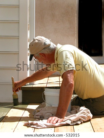 Close up shot of man on knee brushing on deck stain - stock photo