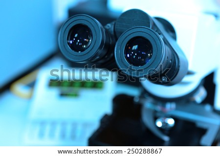 close up shot of microscope at the blood laboratory take with blue filter - stock photo