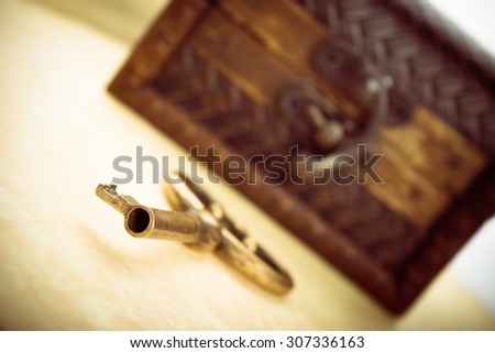 Close-up shot of old metal key and closed wooden treasure chest - stock photo