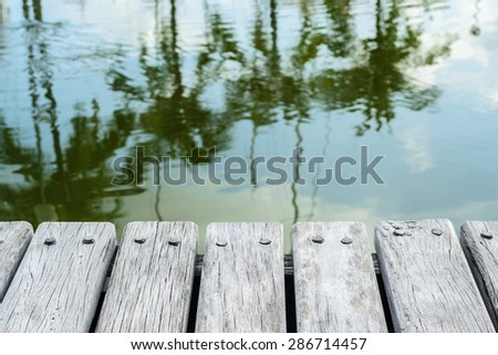 Close up shot of old wooden pier at Phuket boat lagoon marina with coconut tree Reflection - stock photo