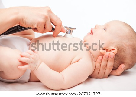 Close-up shot of pediatrician examines three month baby girl. Doctor using a stethoscope to listen to baby's chest checking heart beat - stock photo