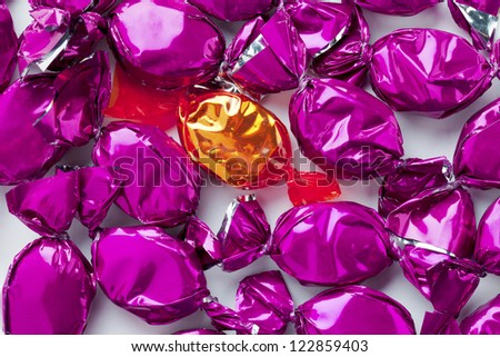 Close-up shot of purple hard candies surrounding a golden candy. - stock photo